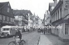 Die damalige Sachsenstrasse ca. 1936 ist mit Kopfsteinpflaster befestigt. Ein Lastwagen steht vor der Gaststätte Zum weissen Schwan. Eine Fahrradfahrerin überquert die Strasse - an dem Lenker des Fahrrads hängt eine Einkaufstasche.