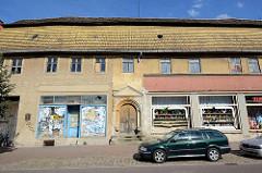 Historisches Lagergebäude, Geschäftshaus mit Dachlüftung und mit Steinen abgedeckten Dachfirst in der Köthener Straße von AKEN / Elbe.