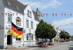Geschäftsstraße in Brunsbüttel - historische Architektur in der Koogstraße, Kaiserhof Stuben - große deutsche Flagge.