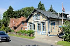 Gründerzeit - Wohnhaus, Fassade mit gelbem Klinker verkleidet, blau abgesetzte Dekorelemente / Säule - im Hintergrund Neubau Klinkergebäude - Architektur in Brunsbüttel, Kreis Dithmarschen.