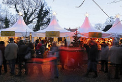 Die Besucher und Besucherinnen schlendern am frühen Abend über den Bergedorfer Weihnachtsmarkt. Die Marktstände sind festlich beleuchtet und mit Tannenbäumen und beleuchteten Sternen geschmückt.