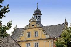 Giebel und Dachturm vom Coswiger SChloss.  Coswig war von 1603 bis 1793 Teil des Fürstentums Anhalt-Zerbst. Das in der Stadt befindliche Schloss wurde 1667–1677 erbaut und diente bis ins 19. Jahrhundert als Witwensitz. Während im Bauschmuck des nördl