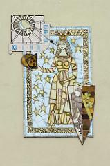 Wappen von Coswig / Anhalt an der Fassade vom Rathaus. In einem blauen mit 12 goldenen Sternen bestreuten Schild steht eine golden gekrönte Frauengestalt.