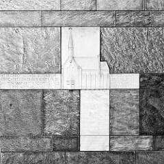 Relief und Inschrift an der Fassade der kath. St. Marien Kirche in Hamburg Bergedorf. Inschrift: Die Pfarrgemeinde St. Marien errichete an dieser Stätte in den Jahren 1882-83 ihr  1. Gotteshaus. Es wurde niedergelegt 1965.