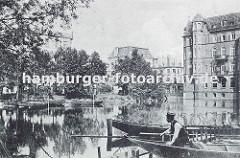 Blick über die aufgestaute Bille - ein Schiffer sitzt in seinem Kahn, dahinter ein Fischerboot mit Reusen an Bord. Am Teichufer am Bergedorfer Markt, Alte Holstenstrasse liegen weitere Schiffe. Rechts ein mehrstöckiges Backsteingebäude der Gründe