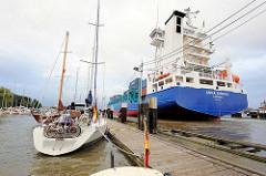 Blick über den Sportboothafen in Brunsbüttel auf die Ausfahrt zur Schleuse vom Nord-Ostsee-Kanal; das Feederschiff Anna Sirkka fährt aus der Schleuse aus; der Containerfrachter hat eine Länge von 134 m und kann 868 TEU / Container transportieren.