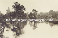 historisches Bild aus Hamburg Bergedorf ca. 1890; ein Mann mit Hut fährt im Ruderboot auf der Bille. Am Flussufer stehen zwischen den Bäumen Bauernhäuser und Fachwerkhäuser, im Hintergrund ist der Kirchturm der St. Petri und Pauli Kirche von Berg