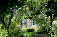 Vorgarten mit Buchsbaumhecken, Laubbäume - Fassade eines Fachwerkgebäudes in der Heiligengeistraße von Bad Oldesloe.