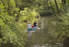 Ein Kanu fährt die Bille flussabwärts Richtung Bergedorf City - die Äste der Erlen und Weiden am Ufer der Bille hängen tief über den Hamburger Fluss und machen so die Kanutour zu einer recht romantischen Fahrt.
