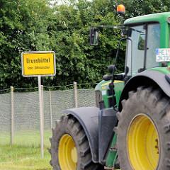 Ortsschild Brunsbüttel, Kreis Dithmarschen - Trecker in Fahrt.