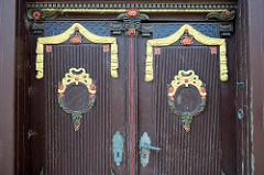 Mit colorierten Schnitzereien versehene Eingangstür eines historisches Bauernhauses - Fachwerkgebäudes in der Reichenstraße von Brunsbüttel Ort / Alt Brunsbüttel.