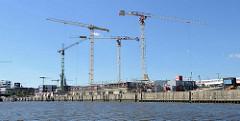 Baustelle / Baukräne am Baakenhafen - Versmannkai in der Hamburger Hafencity; lks. ein die HafenCity Universität..