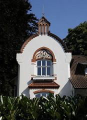 Im Backsteindekor über dem Fenster der Stadtvilla ist ein farbiges Jugendstildekor mit Blüten und geschwungenen Linien angebracht. Dieses Stadthaus gehört zum sogenannten Villenviertel in Hamburg Bergedorf - wohlhabende Hamburger und Bergedorfer