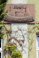 Steinplakette an der Fassade vom Brunsbütteler Rathaus - Stadt Brunsbüttelkoog; Leuchttürme und Kogge.