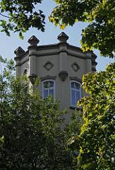 Zwischen den Bäumen ragt im Bergedorfer Villen- viertel ein Turm mitangedeuteten Zinnen empor. Ende des 19.  Jahrhunderts wurde begonnen, das sogenannte Villenviertel zu bebauen - wohlhabende Hamburger und Bergedorfer Bürger ließen dort ihre repr