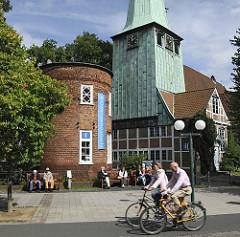 Blick über den Kirchenplatz zum Turm des Hasse - Hauses und der Bergedorfer Kirche St. Petri und Pauli Kirche. Bergedorfer sitzen auf Holzbänken  in der Sonne vor dem historischen Gebäude - Ensemble; Fahrradfahrer fahren auf der verkehrsberuhigte