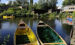 Kanus am Bergedorfer Fluss die Bille, eine Familie mit Kindern starte gerade zu einer Kanufahrt auf der Bille - zwei leere Boote liegen am Bootssteg. Die Bille kann mit dem Kanu flussaufwärts bis Reinbek befahren werden.