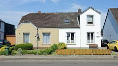 Doppelhaus mit unterschiedlicher Fassadengestaltung - gelber Klinker und weisse Putzfassade, Hecke oder Zaun; Architektur in Brunsbüttel, Kreis Dithmarschen.
