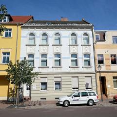 Jugendstil Mietshaus mit floralem Fassadenschmuck; weisse Ziegel mit blauen Zierbändern.