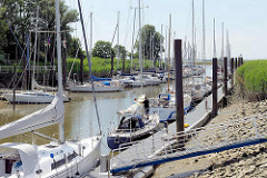 Alter Hafen in Brunsbüttel - Sportboothafen an der Elbe, abhängig von der Tide; Segelboote liegen am Steg.