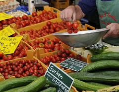 Gemüsestand auf dem Bergedorfer Wochenmarkt - frisches Vierländer Gemüse liegt in Kisten auf dem Verkaufsstand. Im Vordergrund Vierländer Gurken, dahinter die leuchtend roten Vierländer Tomaten. Der Markhändler legt gerade Cherrytomaten in die Wa