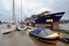 Blick über den Sportboothafen in Brunsbüttel auf die Einfahrt zur Schleuse vom Nord-Ostsee-Kanal; das Feederschiff Emotion fährt in die Schleuse ein; der Containerfrachter hat eine Länge von 170 m und kann 1440 TEU / Container transportieren.