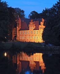 """Das Bergedorfer Schloss in der Abenddämmerung zur """"Blauen Stunde"""". Abends wird das historische Gebäude angestrahlt; Bergedorfer sitzen in der Sommernacht am Wasser der aufgestauten Bille, in dem sich das beleuchtete Schloss spiegelt. Die Ursprüng"""