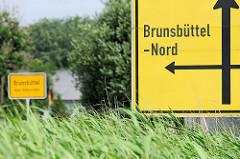Verkehrsschild Hinweis Brunsbüttel Nord - im Hintergrund das Ortsschild.