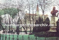 historische Aufnahme aus Bergedorf ca. 1900; rechts die Büste von Kaiser Wilhelm I. auf einem Marmorsockel und im Hintergrund das Bergedorfer Schloss mit dem spitzen Schlossturm. Eine Brücke mit hölzernem Geländer führt über den Schlossgraben.