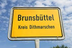 Ortsschild Brunsbüttel, Kreis Dithmarschen - blauer Himmel, Schäfchenwolken.