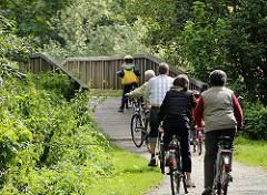 Eine Familie macht auf dem Billewanderweg eine Fahrradtour. Eine Holzbrücke führt die Fahrradfahrer und Fahrradfahrerinnen über den Hamburger Fluss.