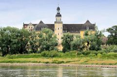 Blick über die Elbe zum Coswiger Schloss. Coswig war von 1603 bis 1793 Teil des Fürstentums Anhalt-Zerbst. Das in der Stadt befindliche Schloss wurde 1667–1677 erbaut und diente bis ins 19. Jahrhundert als Witwensitz. Während im Bauschmuck des nördli