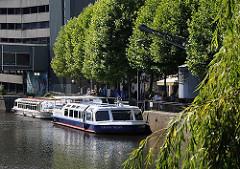 Zwei Ausflugsschiffe der Bergedorfer Schifffahrtlinie liegen an der Kaimauer vom Serrahn - Hafen in der City von Hamburg Bergedorf. Zwischen den Bäumen ragt der Arm des historischen Krans aus den Bäumen heraus. Der elektrische Drehkran steht unte