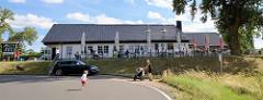 Fährhaus Aken an der Elbe - Gäste sitzen auf der Terrasse in der Sonne, Abfahrt zur Gierseilfähre.