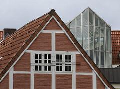 Im Vordergrund ist in der Bergedorfer City der Giebel von einem historisches Fachwerkhaus, dahinter eine moderne Glasfront eines Neubaus.