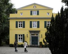 Das Gebäude vom Standesamt Hamburg Bergedorf ist ebenso wie das Bergedorfer Rathaus in einem ockergelben Farbton gestrichen. Die Fenster haben grüne Holzluken unter dem Dachfirst ist das Hamburger Wappen zu sehen.