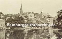 Historisches Foto aus Bergedorf ca. 1890 - Blick über den Hafen, alte Häuser stehen am Wasser, einige Boote liegen am Ufer. In der Bildmitte der Kirchturm der Bergedorfer St. Petris und Pauli Kirche. Rechts die Rückseite der Kornwassermühle mit d
