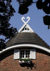 Fachwerkhaus im Bergedorfer Villenviertel; zwei Pferdeköpfe sind auf dem Dach des Hauses als Giebelschmuck angebracht. Im Klinker-Mauerwerk sind mit Steinen Dekore u.a. eine Mühle und ein Besen? gemauert. Vor dem Giebelfenster mit zwei Holzluken