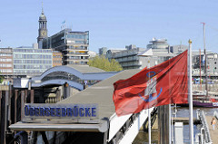Blick auf die Überseebrücke - Fahne vom Hamburger Hafen -  Hafenflagge / Admiralitätsflagge im Wind; im Hintergrund der Kirchturm der St. Michaeliskirche und Teile vom Verlagsgebäude Gruner + Jahr am Baumwall.