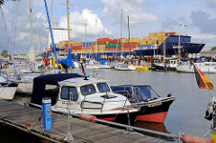 Sportboothafen / Yachthafen Brunsbütte - hinter der Schleuse im Nord-Ostsee-Kanal; Motorboote und Segelboote liegen am Steg, im Hintergrund fährt ein Containerfeeder in die Schleuse ein.