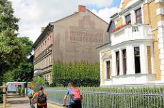 Fassadenrelief mit Dekor und Aufschrift Friedrich Gutewort - Baugeschäft; Architektur der Gründerzeit / Historismus in Lutherstadt Wittenberg.