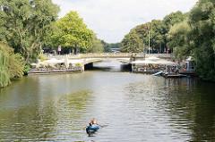 Blick über den Mundsburger Kanal zur Brücke Mundsburger Damm in Hamburg Uhlenhorst. Restaurants auf den Treppen des Anlegers; ein Kanu fährt Richtung Alster.
