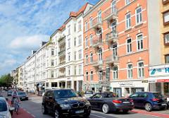 Mühlenkamp in Hamburg Winterhude - Autoverkehr und rot abgesetzte Fahrradwege. Mehrstöckige Wohnhäuser - Geschäfte im Souterrain / Erdgeschoss.