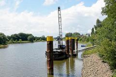 Hafen der Lutherstadt Wittenberg - ein Binnenschiff liegt an Dalben am Ufer; Arbeitsschiff mit Kran.