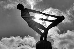 Skulptur Turnende Jungen im Gegenlicht, Schwarz-Weiß Darstellung - Am Exerzierplatz in Norderstedt / Harksheide.
