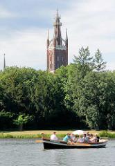 Ruderboot / Gondel auf dem Wörlitzer See - Kirchturm / Bibelturm der St. Petri Kirche in Wörlitz. Die Ende des 12. Jahrhunderts errichtete ursprünglich romanische Kirche wurde unter Fürst Franz von Anhalt-Dessau zwischen 1804 und 1809 im neugotischen