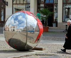 Marktplatz von Lutherstadt Wittenberg - glänzende Metall Erdkugel; Spiegelung der Gebäude am Marktplatz der Lutherstadt Wittenberg.