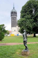 Kirchturm der Schlosskirche von Lutherstadt Wittenberg - Skulptur Badende; nackte Frau mit Handtuch in der Grünanlage.