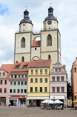 Historische Wohn- und Geschäftshäuser am Marktplatz der Lutherstadt Wittenberg - Kirchtürme der Stadt- und Pfarrkirche St. Marien.