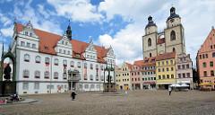 Markt von Lutherstadt Wittenberg - Denkmale von Martin Luther und Philipp Melanchthon. Lks. das Rathaus, erbaut von 1523 - 1535 unter Mitwirkung von Lucas Cranach d. Ä. - re. historische Bürgerhäuser und die Stadtkirche St. Marien.